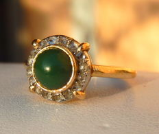 Ring with a jade cabochon in a diamond entourage, mount in 18 kt yellow gold