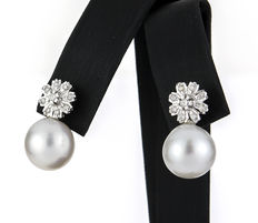 White gold earrings set with brilliant-cut diamonds in a flower design bezel setting and South Sea Australian pearls.