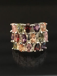 Modern, multi-coloured ring with peridot, garnet, tanzanite, and pink sapphire.