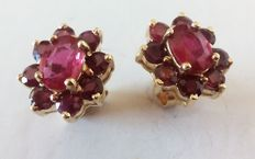 Flower-shaped 18 kt gold earrings, with ruby gemstones in prong settings design.