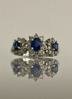 Trilogy ring with sapphires surrounded by diamonds