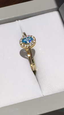Gold ring set with blue topaz