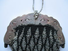 A beaded purse with silver brace.