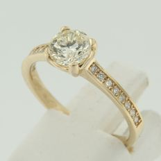 Yellow gold solitaire ring with side stones set with brilliant cut diamonds.