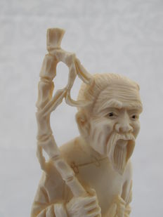 Ivory sculpture of an old man with a bamboo stick and basket, on a wooden base - China - Approx. 1930
