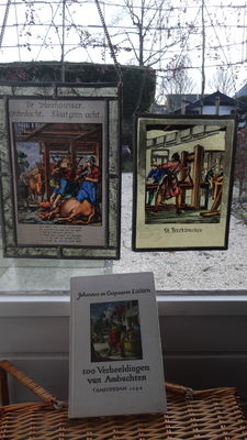 "Two stained glass hangers depicting the craft ""Vleeshouwer"" (butcher) and the book printer, comes with a book containing 100 illustrations of various crafts."