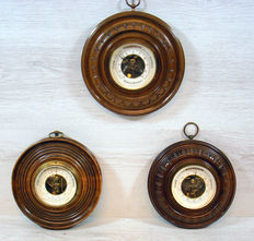 Three - round barometers - on hand carved wooden background