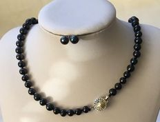 Necklace made of knotted black saltwater pearls with unusually designed silver clasp & matching earrings