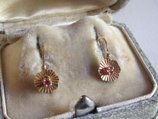 Small 'sleeper' earrings in yellow gold with small rubies set between prongs.