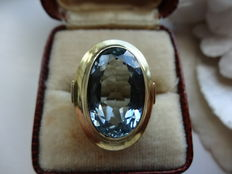Gold ring with light blue topaz.