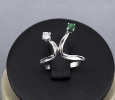 White gold ring with a diamond and an emerald.