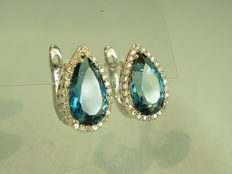 Earrings with blue topazes and white topaz entourage