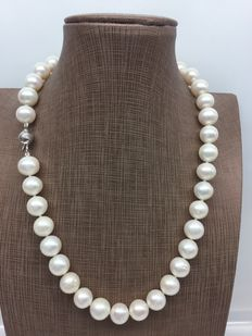 Necklace composed of 11 mm white cultured freshwater pearls, with 18 kt gold clasp.