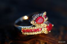 Silver ring with rubies and many small sapphires