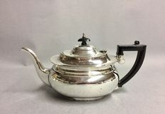 A silver plated tea pot with a bakelite handle and knob.