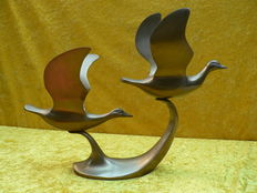 Bronze/brass sculpture of two ducks in flight.