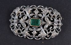 Brooch in yellow gold and silver, with central emerald and diamonds.