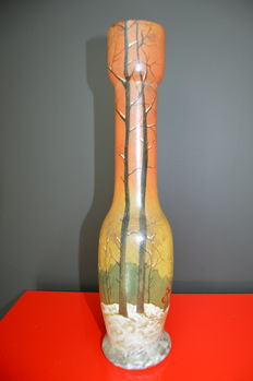 François-Théodore Legras (1839-1916) -  Tulip vase with long neck, opacified orangy background with an enameled decor of a peasant leaving her snowy village.