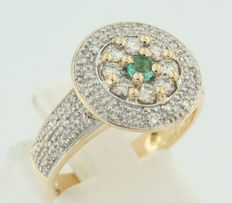 18 kt bi-colour gold entourage ring set with a central emerald and an entourage of brilliant cut diamonds.