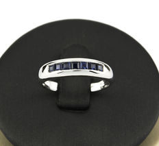 White gold ring set with carré-cut sapphire gemstones.