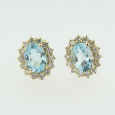 Yellow gold rosette ear studs set with blue topaz and brilliant cut diamonds at the entourage