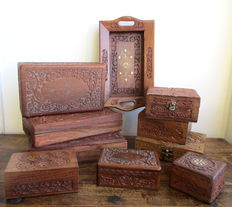 Nine hand-carved wooden boxes + a tray in a floral pattern