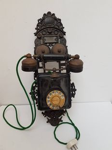 Antique Bakelite wall telephone on a cast iron back plate - Netherlands - 1920/30