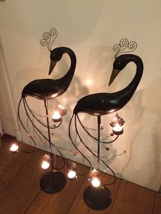 Two iron sculptures of cranes, with lights