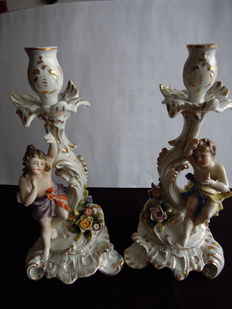 Two porcelain candle holders adorned with putti figures and floral effects