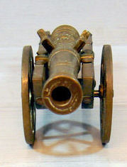 Miniature bronze cannon on a  wooden gun carriage with bronze wheels.