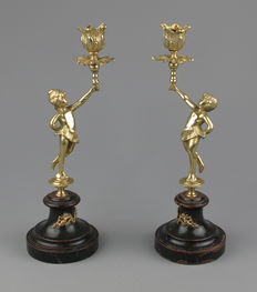 A pair of gold-plated candlesticks on wooden base -  boy and girl - France - ca. 1900
