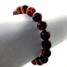 Classic bracelet of dark Baltic amber round beads of 11 mm in diameter