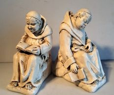 A pair of bookends: a sleeping and reading monk