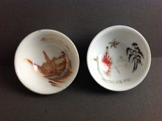 Two very fine Japanese Imperial Army sake commemorative cups with an image of artillery, a machine gun and the Japanese rising sun flag