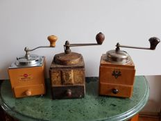 Three old hand coffee grinders of wood and metal