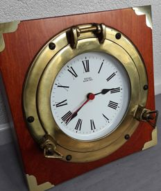 Royal Marine ship's clock in a brass porthole on a heavy wooden frame
