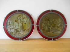 Two round stained glass window decorations on wooden display stand with festive old Dutch scenes