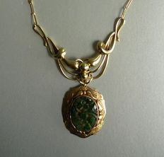 14 kt yellow gold vintage pendant with cut green Jade stone with floral decorations on a golden necklace