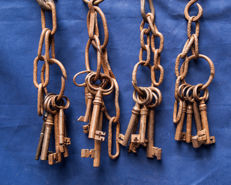 Twenty 17th and early 18th century iron keys to four key rings and necklaces