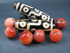 Two 9 eye agate dzi beads together with six carnelian prayer beads - Himalayan regions - third quarter of the 20th to early 21st century.
