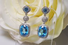 Pair of 14 kt white gold dangle earrings with approx. 9 ct in diamonds and topaz.
