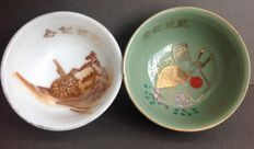 Two very nice Japanese Imperial Army sake commemorative cups, with images of artillery, a helmet, the Japanese flag, guns, and cherry blossom