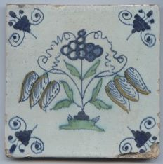 Antieke tile with a depiction of grapes - tulips or chess flowers