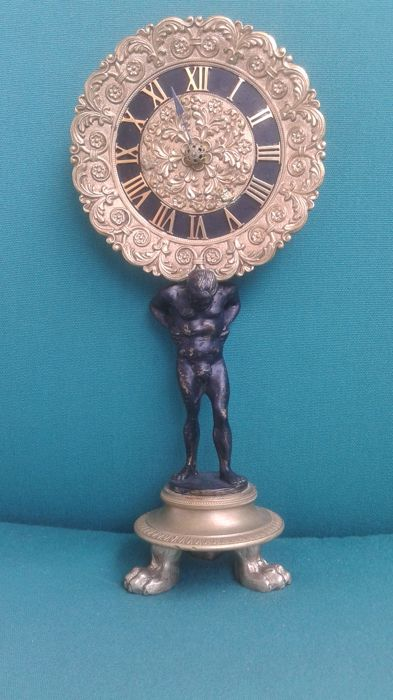 Bronze clock - nude male as the Atlas statue, wearing a rosette-shaped watch - the base with  three lion paws - Empire 1st century 19th century