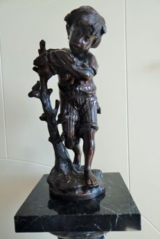 Bronze - statue of a boy on a tree trunk