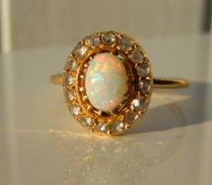 Old ring with luminous opal and 16 diamonds on 18 kt yellow gold