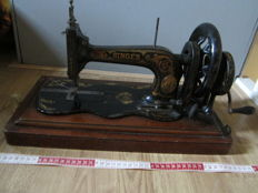 Antique Singer sewing machine with wooden dust cover, circa 1880