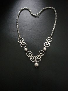 Vintage designer silver necklace with beads and rings, attached to an original necklace