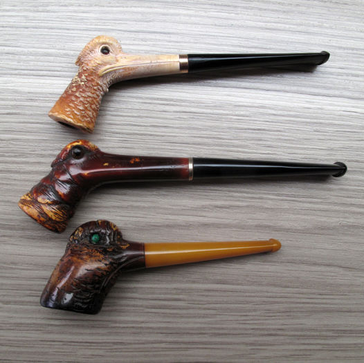 3 meerschaum pipes presenting a woodpecker