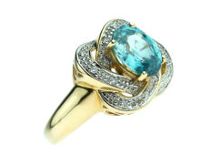 14 kt yellow gold fantasy women's ring set with 12 diamonds and a blue zirconia; ring size is 18.25